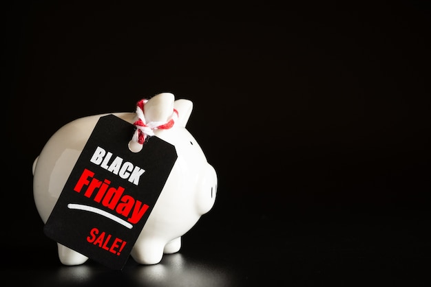 Shopping sale concept with red ticket black friday sale tag hanging with piggy bank