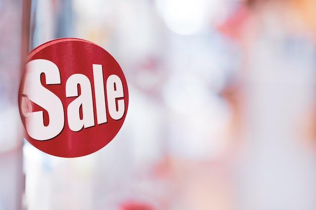 Концепция скидки продажи покупок, красная этикетка сбывания на полке универмага покупок с предпосылкой bokeh с космосом экземпляра.
