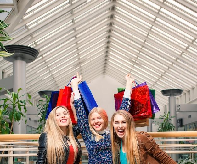 쇼핑, 판매, 행복한 사람들, 관광 개념 - 쇼핑몰에 쇼핑백을 든 아름다운 세 소녀