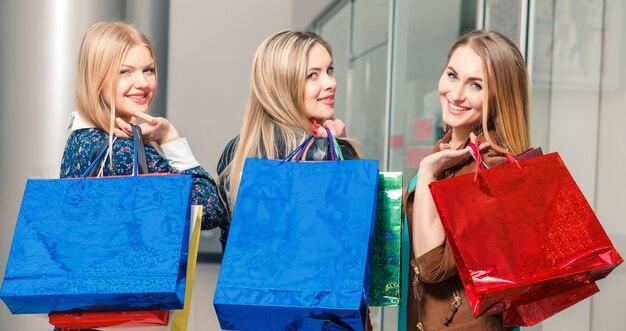 쇼핑, 판매, 행복한 사람들, 관광 개념 - 쇼핑백을 든 세 명의 아름다운 소녀들이 쇼핑몰에서 뒤를 돌아보았다
