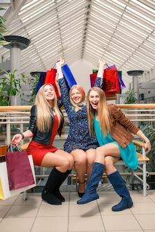 쇼핑, 판매, 행복한 사람들, 관광 개념 - 쇼핑백을 들고 쇼핑몰에 앉아 있는 세 명의 아름다운 소녀