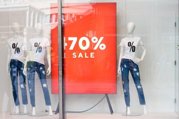 セールのサインが入ったtシャツを着たマネキン、店内のダミー、セール、ファッションコンセプトのショッピングセールウィンドウディスプレイ。