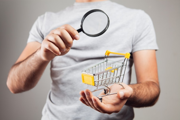 Shopping search concept. magnifying glass looking at the basket on gray background