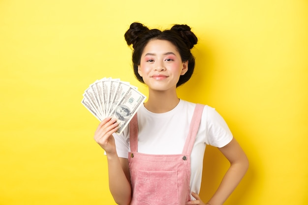 Shopping. smiling asian girl with stylish makeup, showing dollar bills with pleased face, making money, standing on yellow background