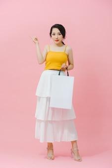白いパケットを保持しているショッピング笑顔のファッションの女性。