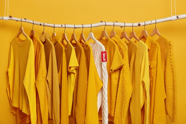 Shopping and special offer concept. many yellow clothes items and white knitted sweater with red tag sale.