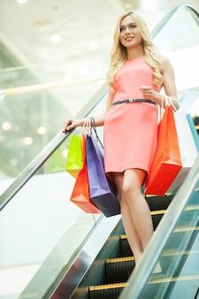 Шоппинг. красивая молодая женщина, стоящая на эскалаторе и несущая хозяйственные сумки
