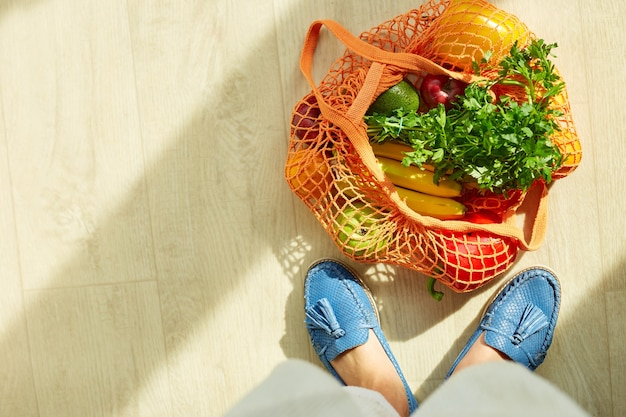 緑の靴の女性の足の上面図と自宅の日光の床に新鮮な果物や野菜でいっぱいのショッピングストリング食料品再利用可能なメッシュバッグコンセプト健康的なビーガンを食べるゼロウェイスト