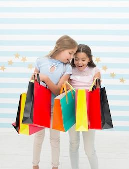 Шоппинг, место для развлечений. симпатичные маленькие покупатели. очаровательные девушки, глядя в хозяйственные сумки. маленькие дети любят делать покупки. покупки для реальной жизни.
