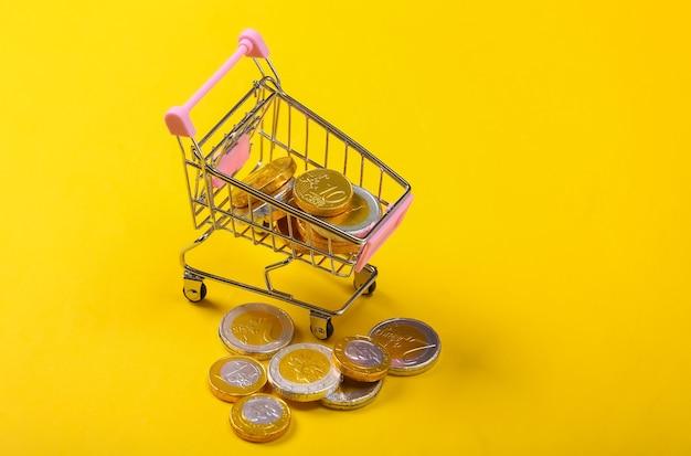 Торговая тема. мини-тележка для супермаркета с монетами на желтом.