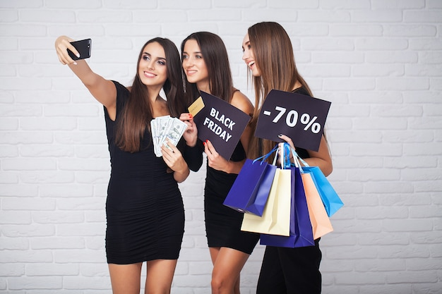 Shopping. three women holding colored bags in black friday sales