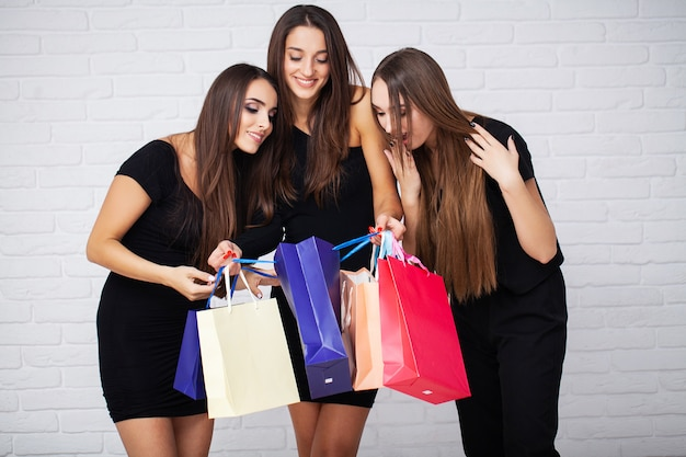 Shopping. three women holding colored bags on light  in black friday holiday