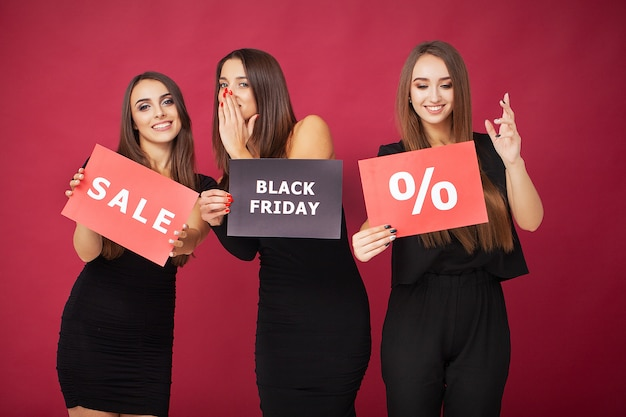 Shopping. three women holding discount blank on red  in black friday holiday