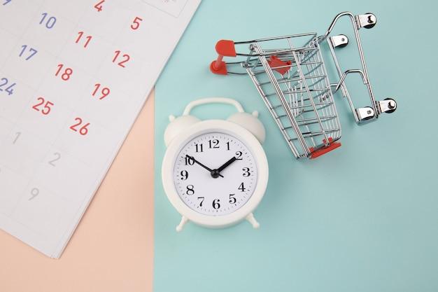 쇼핑 시간 개념. 알람 시계와 달력이있는 슈퍼마켓 트롤리.