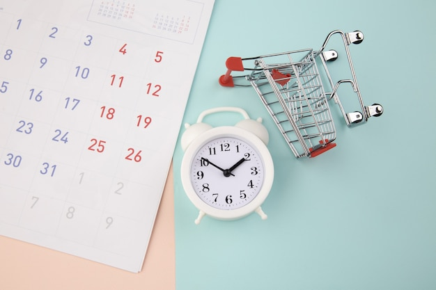 Shopping time concept. supermarket trolley with alarm clock and calendar. top view.