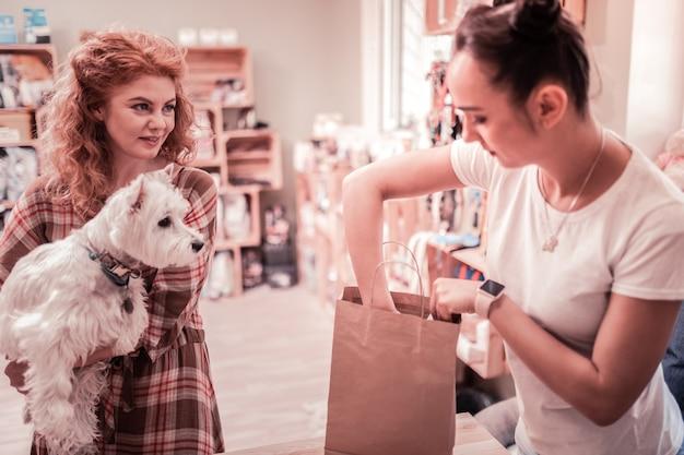 ショッピングタイム。買い物中に彼女の白いふわふわの犬を保持している真鍮の髪の巻き毛の女性