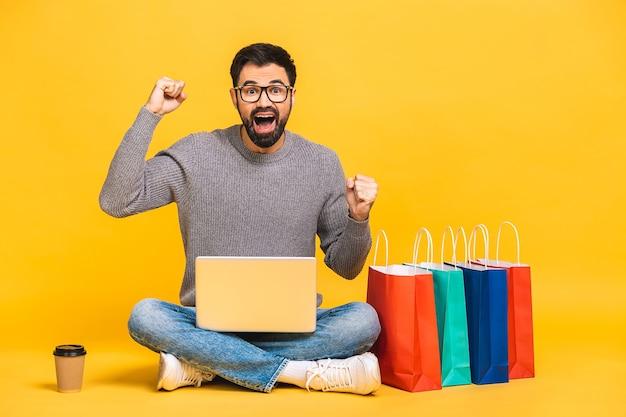 ショッピングタイム!黄色の背景で隔離の床に座っている間ラップトップコンピューターを保持しているショッピングパッケージを持つ幸せな若いひげを生やした男の肖像画。
