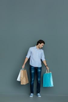 ショッピングタイム。お店を訪問しながら笑顔で彼のバッグを見て前向きな幸せな喜びの男