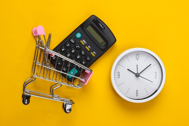 Время для покупок. тележка супермаркета с калькулятором, часами на желтой поверхности. минимализм. вид сверху
