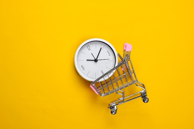 Время для покупок. тележка супермаркета с часами на желтом фоне. минимализм. вид сверху