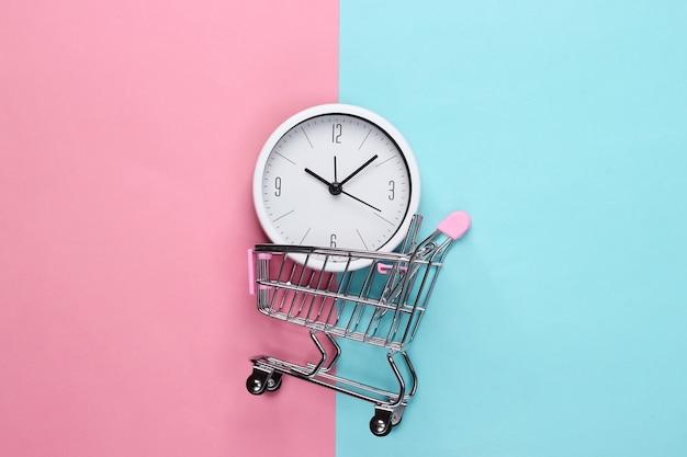 Время для покупок. тележка супермаркета с часами на розовом синем фоне. минимализм. вид сверху