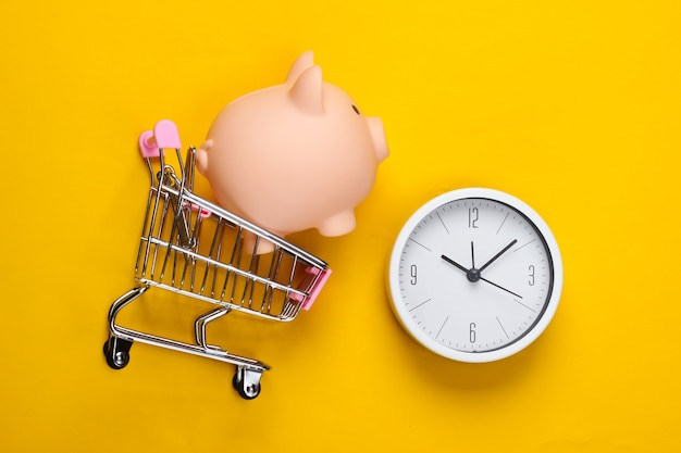Время для покупок. тележка супермаркета с копилкой, часами на желтом фоне. минимализм. вид сверху