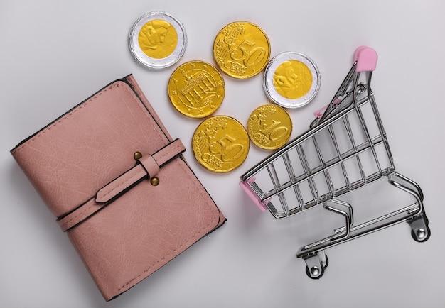 Время для покупок. тележка супермаркета с кошельком, монеты на белом