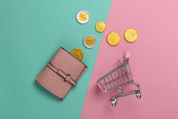 Время для покупок. тележка для супермаркета с кошельком, монеты на розовом синем
