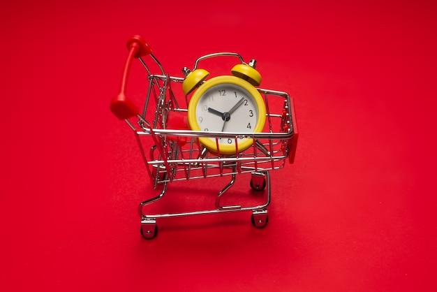 Время для покупок. желтый будильник в корзине для покупок на красном фоне. скопируйте пространство.