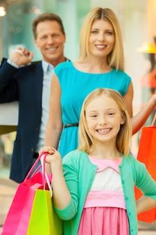 一緒に買い物をするのは楽しいです。ショッピングバッグを持って、ショッピングモールに立っている間カメラに微笑んで陽気な家族