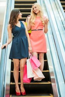 Ходить по магазинам вместе - это весело. две девушки стоят на эскалаторе и несут сумки с покупками