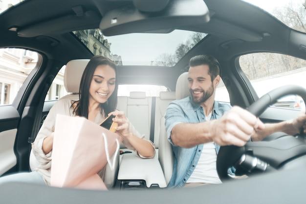 함께 쇼핑. 앞 조수석에 앉아 매력적인 남자가 차를 운전하는 동안 웃는 젊은 아름다운 커플