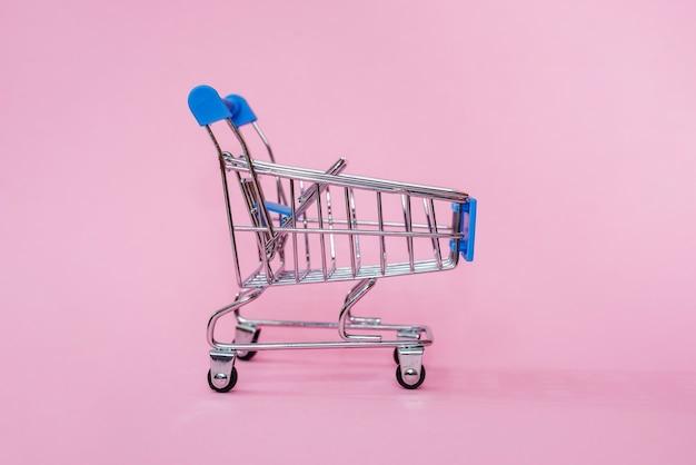 ピンクのパステルカラーの美しいファッショナブルな背景のショッピングおもちゃのカート。ショッピングのコンセプト。