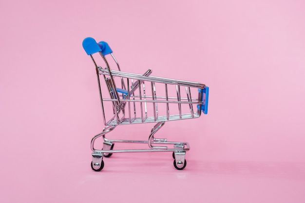 Shopping toy cart on pink pastel beautiful fashionable background. shopping concept.