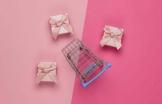 핑크 파스텔 배경에 리본으로 쇼핑 트롤리 및 선물 상자. 크리스마스, 생일 또는 결혼식을위한 구성. 평면도