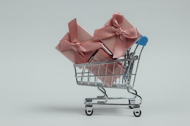 Тележка для покупок и подарочные коробки с бантами на белом фоне. композиция на рождество, день рождения или свадьбу.
