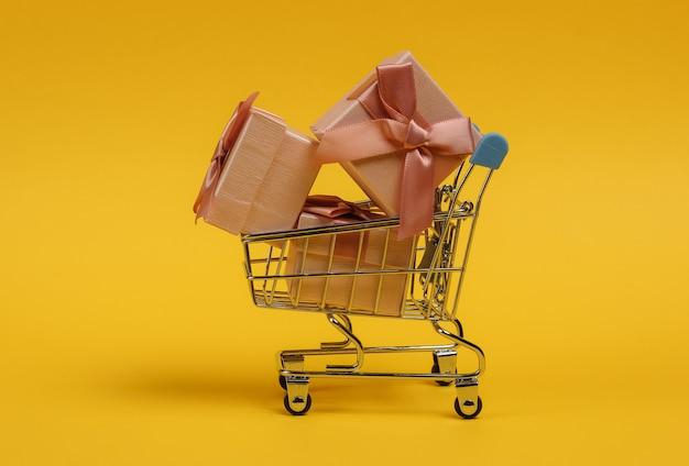 Тележка для покупок и подарочные коробки с бантами на желтом фоне. композиция на рождество, день рождения или свадьбу.