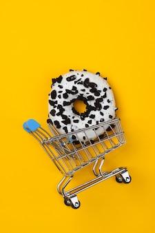 쇼핑 트롤리와 유약을 바른 도넛은 노란색 바탕에 초콜릿 조각을 뿌렸습니다. 과자 케이크, 건강에 해로운 음식. 평면도
