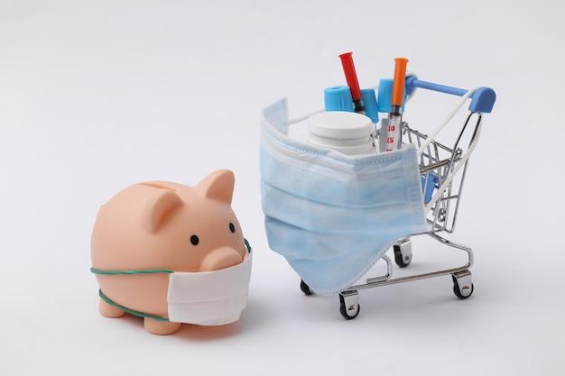 파란색 배경에 시험관, 주사기, 약병이 있는 의료용 마스크를 쓴 쇼핑 트롤리와 돼지 저금통. 보건 의료