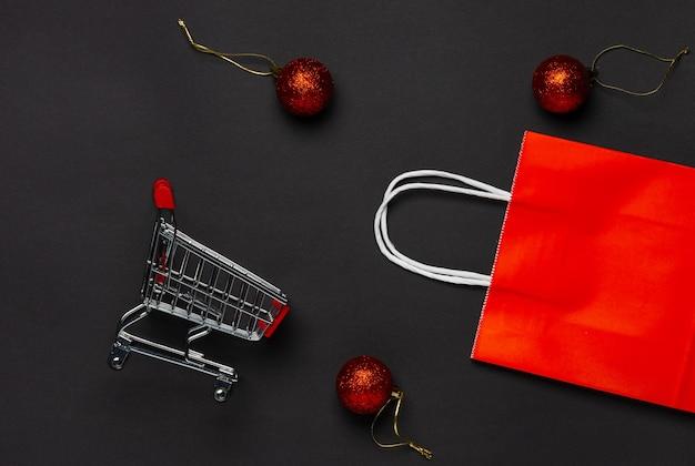 Тележка для покупок и красный пакет на красном на черном.