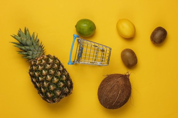 노란색 배경에 쇼핑 트롤리와 열대 과일. 슈퍼마켓에서 쇼핑. 건강 식품 개념