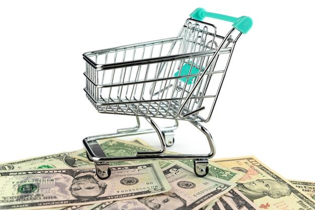 ショッピングトロリーと白い背景、コマースの概念に分離された米ドル紙幣