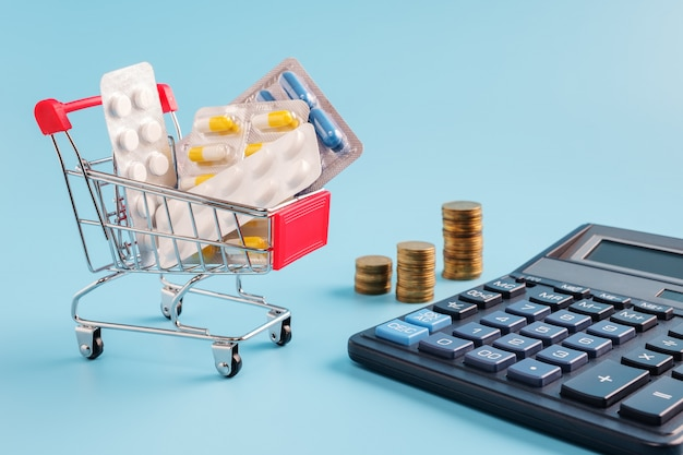 Shopping trolley cart filled medicinal tablets, stacks of coins in row on blue background.