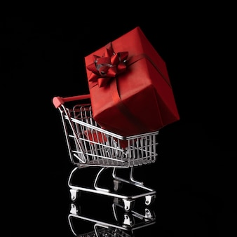Shopping trolley cart and gift box on black background. buying presents concept, online shopping. isolated, instagram, copy space