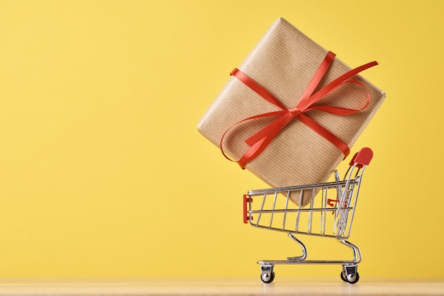 Shopping trolley cart and gift on yellow background
