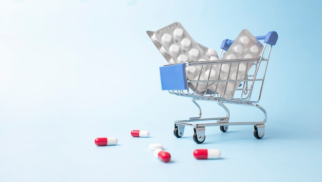 Shopping trolley cart made by pills on light blue surface