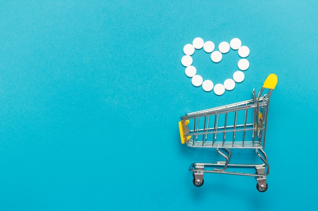 Shopping trolley cart with assorted medicine pills one blue background.