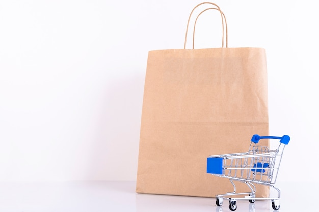 Shopping trolley, craft paper bag, on a white wall. copy space.