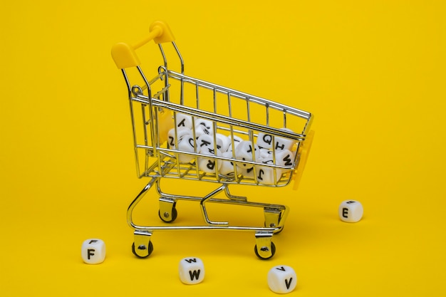 Shopping trolley and cubes with letters on a yellow background