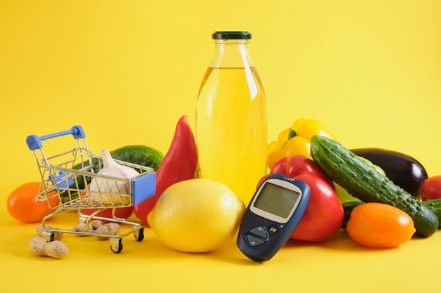 Тележка для покупок, цифровой глюкометр и овощи на желтом фоне. диета при диабете, пищевая корзина для диабетиков